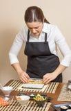 Stående av kvinnakocken som rullar upp en japansk sushi Royaltyfria Bilder