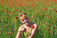 Stående av kvinnan av genomsnittliga år med den röda vallmo i en hand Arkivfoton