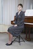 Stående av kvinnan i Front Of Piano Fotografering för Bildbyråer