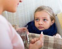 Stående av kvinnan med antibiotikummen och barnet som har influensa royaltyfri bild
