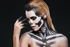 Stående av kvinnan med makeup för blont hår och halloween skelett arkivfoto