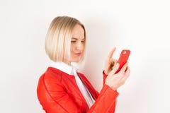Stående av kvinnan med mobiltelefonen i rött omslag på vit bakgrund royaltyfria bilder