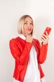 Stående av kvinnan med mobiltelefonen i rött omslag på vit bakgrund royaltyfria foton