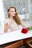Stående av kvinnan med scharlakansrött ros som spelar pianot arkivfoto