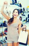 Stående av kvinnan med shoppingpåsar som har valt skor i han arkivfoton