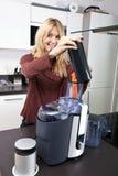 Stående av kvinnan som använder juiceren för juicing morötter på diskbänken Royaltyfri Fotografi