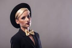 Stående av kvinnan som bär en dräkt och en hatt Fotografering för Bildbyråer