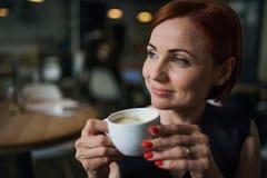 Stående av kvinnan som har sammanträde i ett kafé som rymmer en kopp kaffe royaltyfri bild