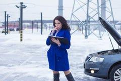 Stående av kvinnan som läser en manuell bil Arkivfoto
