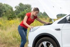 Stående av kvinnan som ser under huven av den brutna bilen på lantligt Royaltyfria Foton