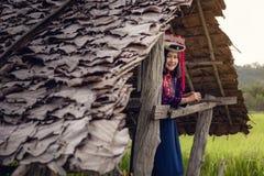 Stående av kvinnan stam- Lisu i traditionell kläd- och smyckendräkt i stuga , Livsstil av kullestamflickan i norden royaltyfri bild