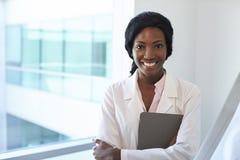 Stående av kvinnlig doktor With Digital Tablet i examenrum arkivfoto