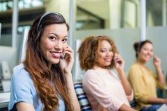 Stående av kvinnliga kundtjänstledare som talar på hörlurar med mikrofon på skrivbordet Arkivfoto