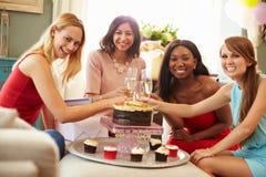 Stående av kvinnliga vänner som hemma firar födelsedag fotografering för bildbyråer
