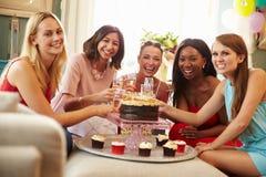 Stående av kvinnliga vänner som hemma firar födelsedag royaltyfria foton