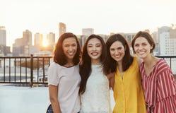 Stående av kvinnliga vänner som samlas på takterrassen för parti med stadshorisont i bakgrund fotografering för bildbyråer