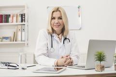 Stående av kvinnligt doktorssammanträde på skrivbordet royaltyfria bilder