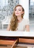 Stående av kvinnligt sammanträde på pianot royaltyfri foto