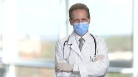 Stående av läkaren i skyddande maskering med korsade armar arkivfilmer