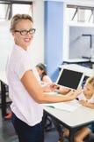 Stående av lärareanseendet med den digitala minnestavlan i klassrum arkivbild