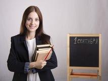 Stående av läraren med läroböcker och brädet i bakgrunden Arkivfoton