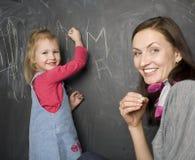 Stående av läraren och liten student, moder och dotter nära svart tavla Fotografering för Bildbyråer