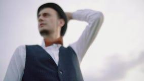 Stående av le för ung man som av naturen omges Man som slitage en hatt långsam rörelse stock video