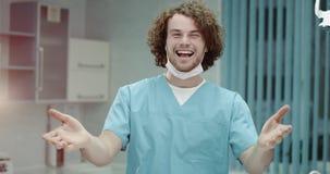 Stående av le kirurger eller doktorn för en ung man som sätter på kirurgisk maskering och ser raka till kameran stock video