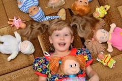 Stående av lilla flickan (barn, unge) med dockor på mattan Arkivbild