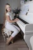 Stående av lilla flickan i den vita klänningen som spelar pianot Arkivbild