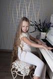Stående av lilla flickan i den vita klänningen som spelar pianot Arkivfoton