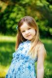 Stående av lilla flickan i en blå klänning i sommarträdgård Royaltyfri Fotografi