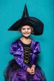 Stående av lilla flickan i kläder för svart hatt och häxa halloween fe saga Studiostående på blå bakgrund Fotografering för Bildbyråer
