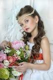 Stående av lilla flickan med blommor fotografering för bildbyråer