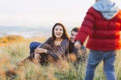 Stående av lilla flickan med en rolig hatt och fader och mal Fotografering för Bildbyråer