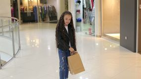 Stående av lilla flickan med långt lockigt hår i en köpcentrum med packar arkivfilmer