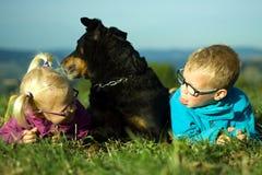 Stående av lilla flickan och pojken med den utomhus- hunden Royaltyfri Bild