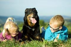 Stående av lilla flickan och pojken med den utomhus- hunden Arkivfoto