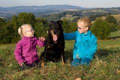 Stående av lilla flickan och pojken med den utomhus- hunden Fotografering för Bildbyråer