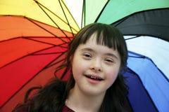Stående av lilla flickan som ler på bakgrund av paraplyet Arkivfoto