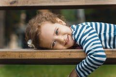 Stående av lilla flickan som ligger på bänk i en parkera, royaltyfri foto