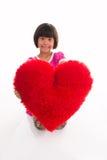 Stående av lilla flickan som rymmer röd hjärta över asiat Arkivbilder