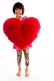 Stående av lilla flickan som rymmer röd hjärta över asiat Arkivbild