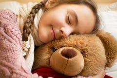 Stående av lilla flickan som sover på brun nallebjörn arkivfoto