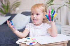 Stående av lilla flickan som spelar med målarfärger royaltyfria foton