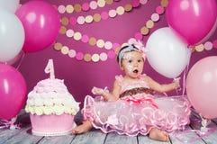 Stående av lite den gladlynta födelsedagflickan med den första kakan Äta den första kakan Dundersuccékaka royaltyfri bild