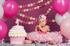 Stående av lite den gladlynta födelsedagflickan med den första kakan Äta den första kakan Dundersuccékaka royaltyfri foto
