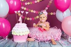 Stående av lite den gladlynta födelsedagflickan med den första kakan Äta den första kakan Dundersuccékaka fotografering för bildbyråer