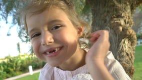 Stående av lite den tandlösa flickan lager videofilmer