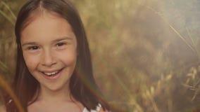 Stående av lite flickan i ett fält av högväxt gräs på solnedgången arkivfilmer